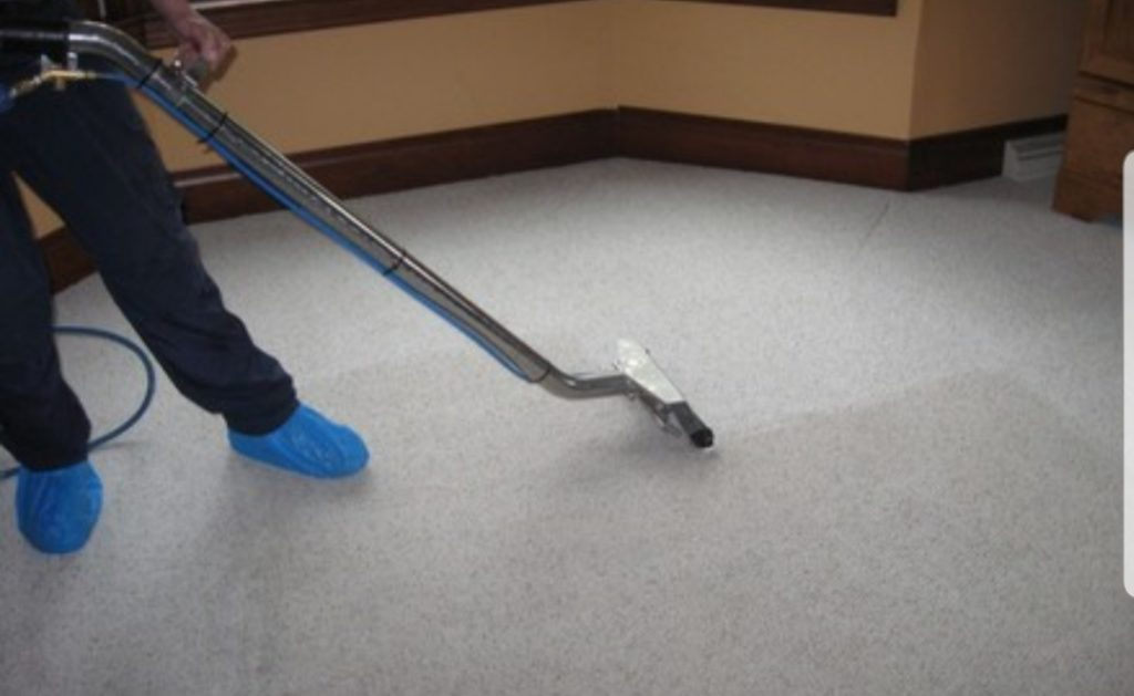 man cleaning carpet with carpet cleaning equipment